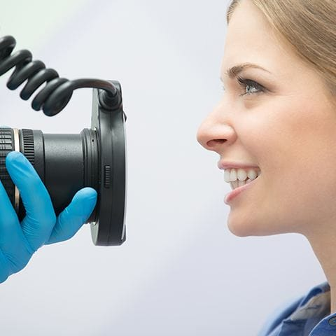 Dentist using digital photography to capture patient's smile