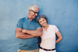 Smiling couple against blue wall