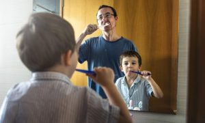 A father and son brushing their teeth together.
